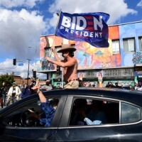 A man waves a Biden flag from his car as people take to the streets in Los Angeles on Nov. 7, 2020 to celebrate Joe Biden and the Democratic Party's victory in the 2020 presidential election.   Frederic J. Brown/AFP via Getty Images