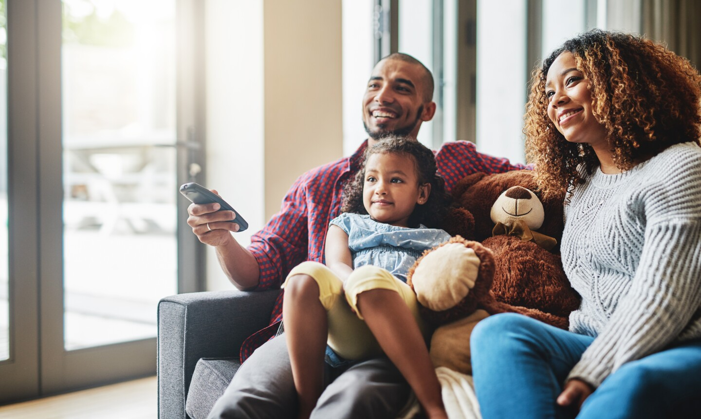 Cropped shot of a happy young family of three watching tv together in their living room at home